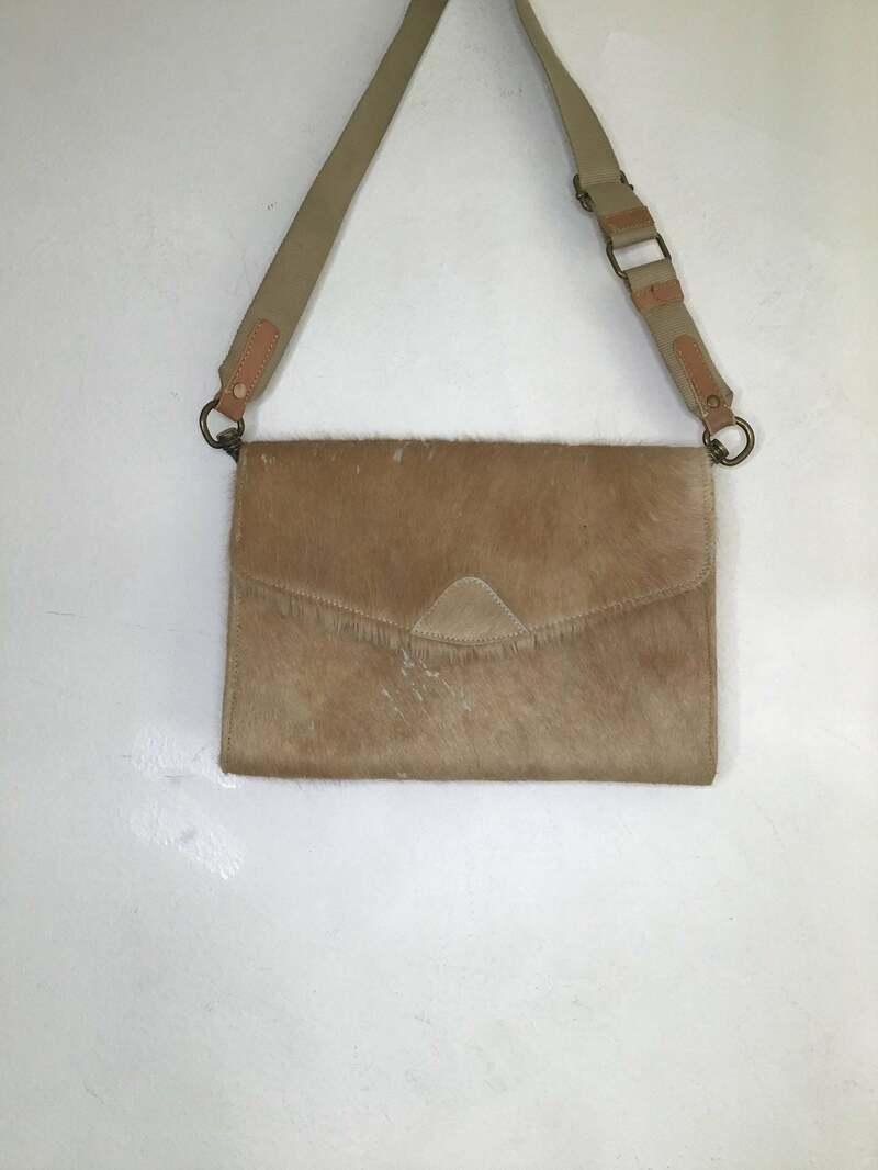 Buy Vintage style cow skin bag beige color on the handle fastened on magnet button have zipper pocket inside.